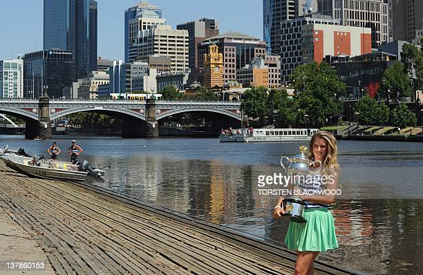Victoria Azarenka of Belarus poses with the Australian Open women's singles trophy along the Yarra river in Melbourne on January 29 2012 following...