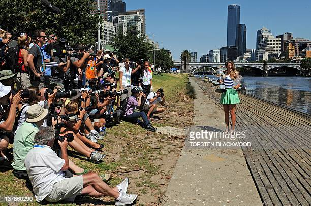 Victoria Azarenka of Belarus poses with the Australian Open women's singles trophy and one for being the top ranked women's player for photographers...