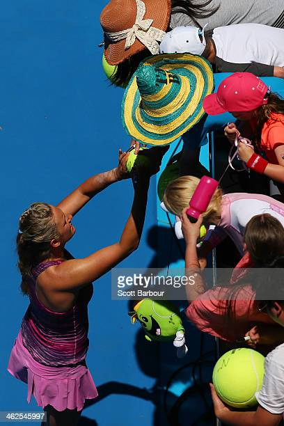Victoria Azarenka of Belarus signs autographs after winning in her first round match against Johanna Larsson of Sweden during day two of the 2014...