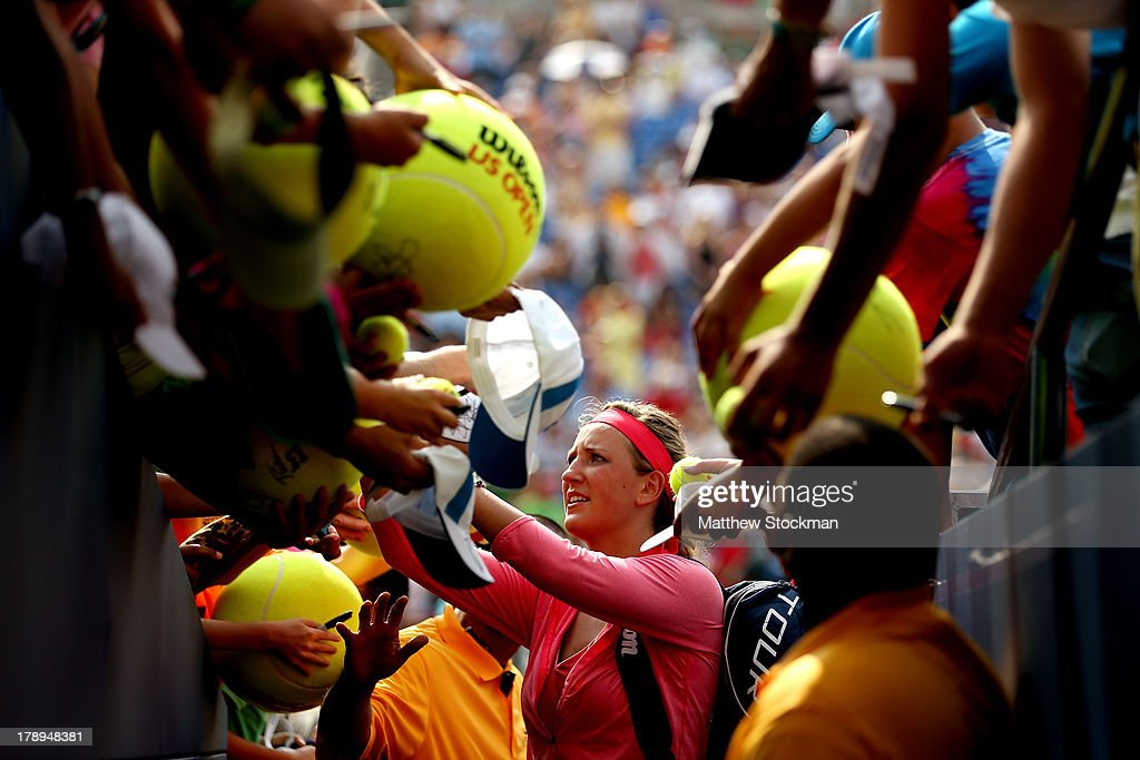 Victoria Azarenka of Belarus signs autographs for fans following her victory in the women's singles third round match against Alize Cornet of France on Day Six of the 2013 US Open at USTA Billie Jean King National Tennis Center on August 31, 2013 in the Flushing neighborhood of the Queens borough of New York City.