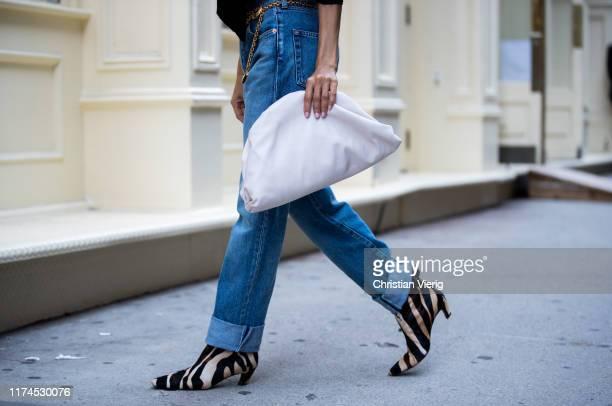 Victoria Barbara is seen wearing black Khaite boots with animal print Balenciaga denim jeans Bottega Veneta clutch during New York Fashion Week...