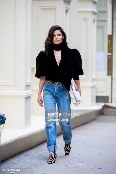 Victoria Barbara is seen wearing black Khaite top and boots with animal print Balenciaga denim jeans Bottega Veneta clutch during New York Fashion...