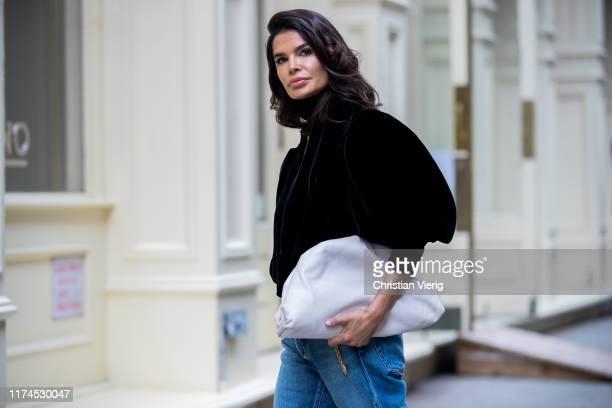 Victoria Barbara is seen wearing black Khaite top Balenciaga denim jeans Bottega Veneta clutch during New York Fashion Week September 2019 on...