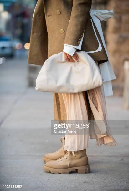 Victoria Barbara is seen wearing Fendi blazer, Max Mara pleated skirt, white Bottega bag, boots by Prada during New York Fashion Week Fall / Winter...