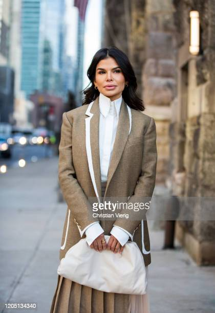 Victoria Barbara is seen wearing Fendi blazer, white Givenchy blouse, Max Mara pleated skirt, white Bottega bag during New York Fashion Week Fall /...