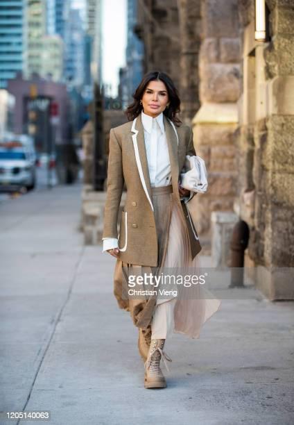 Victoria Barbara is seen wearing Fendi blazer, white Givenchy blouse, Max Mara pleated skirt, white Bottega bag, boots by Prada during New York...