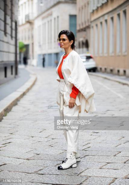 Victoria Barbara is seen wearing Jil Sander cape, orange knit, white pants, bag and Chanel boots during Milan Fashion Week Spring/Summer 2020 on...