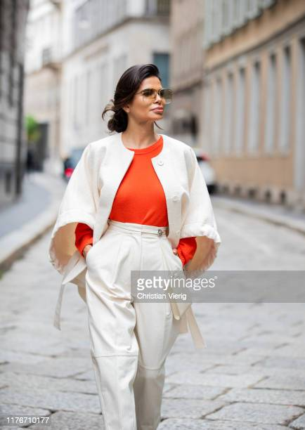 Victoria Barbara is seen wearing Jil Sander cape, orange knit, white pants, bag during Milan Fashion Week Spring/Summer 2020 on September 22, 2019 in...