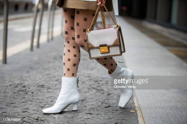 Victoria Barbara is seen wearing olive white two tone blazer, tights with print, bag and white boots all Fendi during Milan Fashion Week...