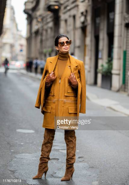 Victoria Barbara is seen wearing orange brown Max Mara jacket zipped dress with pockets turtleneck and brown gloves wild leather boots Saint Laurent...
