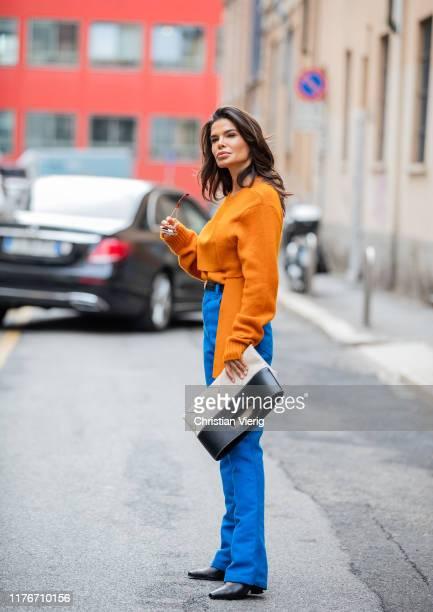 Victoria Barbara is seen wearing orange knit, blue pants, creme white black two tone bag, black shoes all Bottega Veneta during Milan Fashion Week...