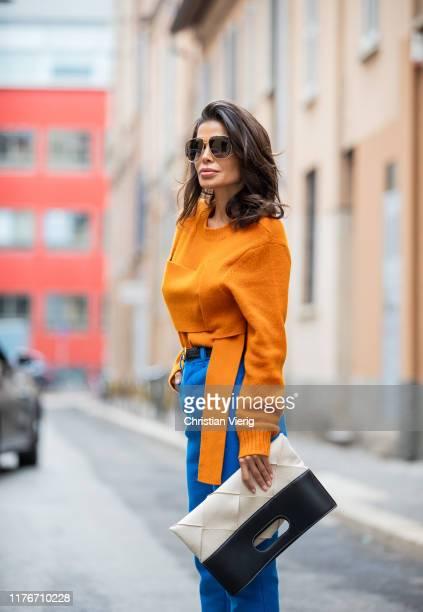 Victoria Barbara is seen wearing orange knit, blue pants, creme white black two tone bag all Bottega Veneta during Milan Fashion Week Spring/Summer...