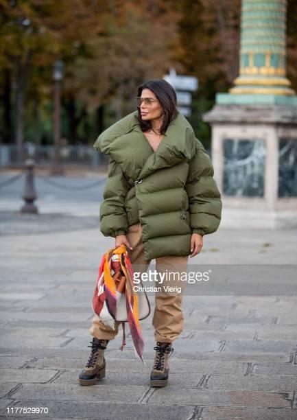 Victoria Barbara is seen wearing total look Loewe green asymmetric down feather jacket, beige pants, Louis Vuitton boots during Paris Fashion Week...
