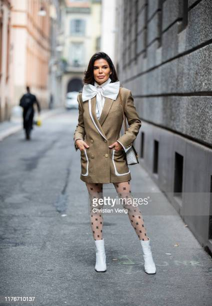 Victoria Barbara is seen wearing white blouse with bow tie, olive white two tone blazer, tights with print, bag and white boots all Fendi during...
