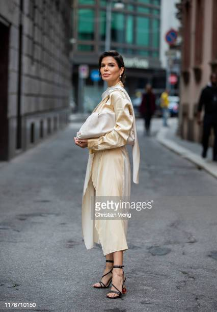 Victoria Barbara is seen wearing white pouch bag, yellow white two tone wrapped dress Bottega Veneta, Jacquemus heels during Milan Fashion Week...