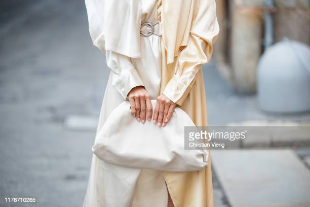 Victoria Barbara is seen wearing white pouch bag, yellow white two tone wrapped dress Bottega Veneta during Milan Fashion Week Spring/Summer 2020 on...