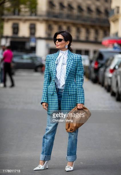 Victoria Barbara seen wearing total look Balenciaga striped blouse with bow tie blue checkered blazer denim jeans white heels brown pouch bag Bottega...