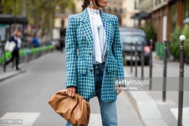 Victoria Barbara seen wearing total look Balenciaga striped blouse with bow tie blue checkered blazer denim jeans brown pouch bag Bottega Veneta...
