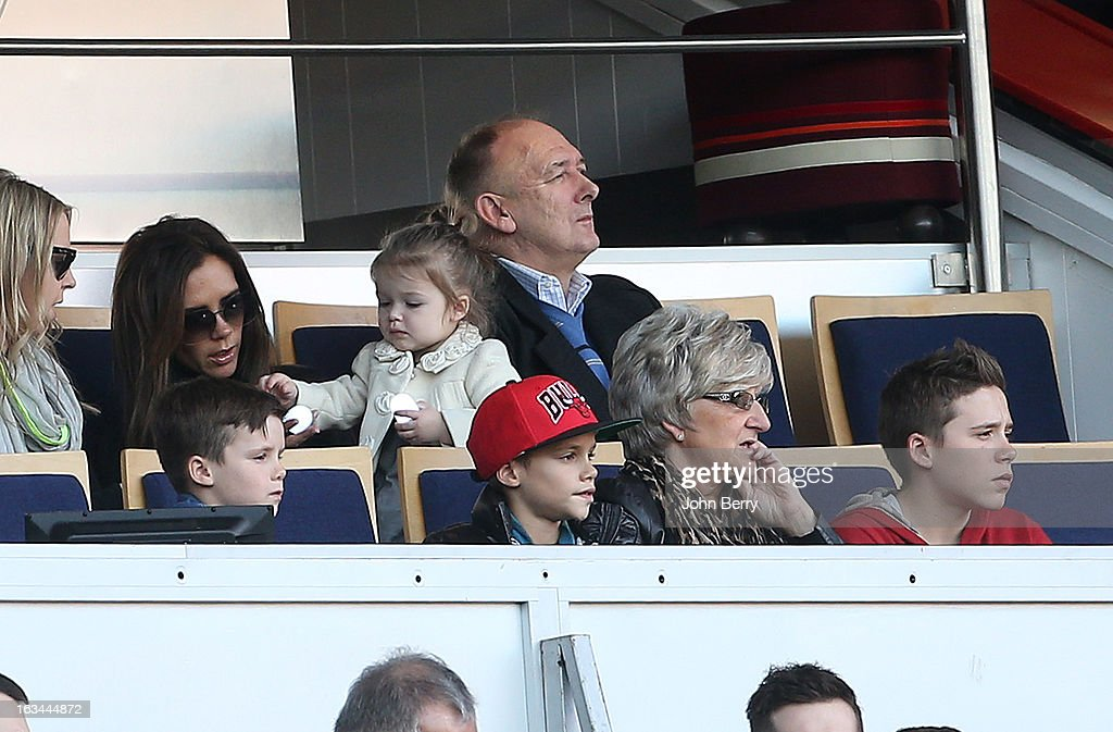 Victoria Beckham, holding her daughter Harper Beckham, Ted Beckham, David's father, below Cruz Beckham, Romeo Beckham, Sandra Beckham, David's mother and Brooklyn Beckham watch the french Ligue 1 match between Paris Saint-Germain FC and AS Nancy-Lorraine ASNL at the Parc des Princes stadium on March 9, 2013 in Paris, France.