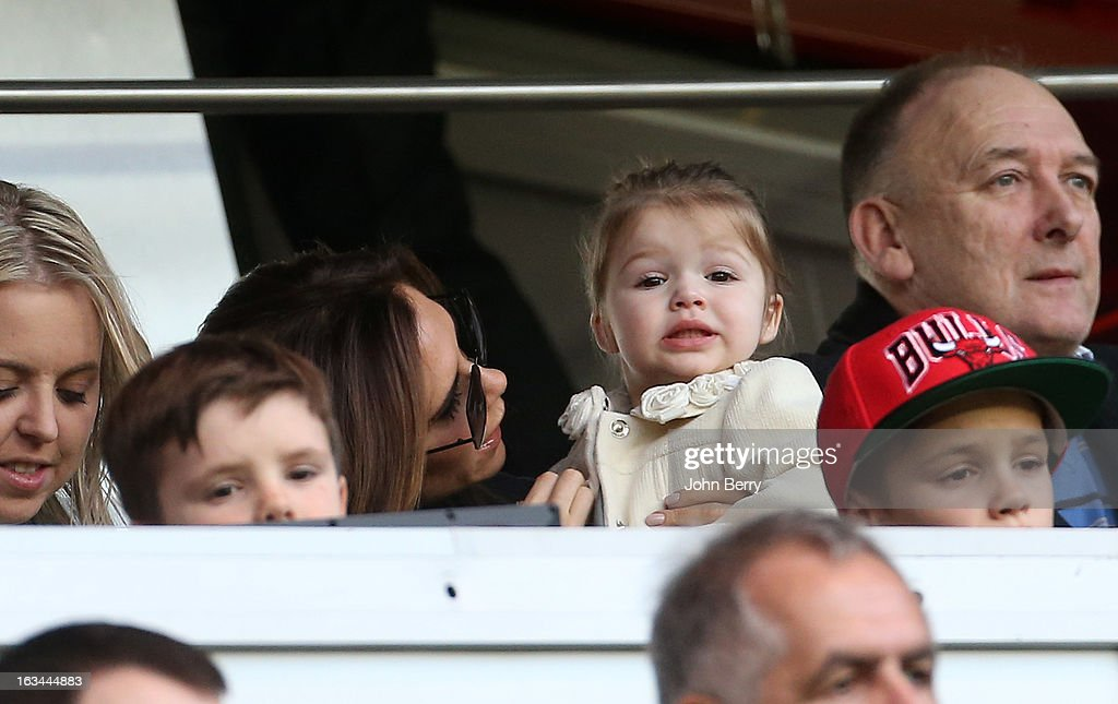 Victoria Beckham holds her daughter Harper Beckham during the french Ligue 1 match between Paris Saint-Germain FC and AS Nancy-Lorraine ASNL at the Parc des Princes stadium on March 9, 2013 in Paris, France.