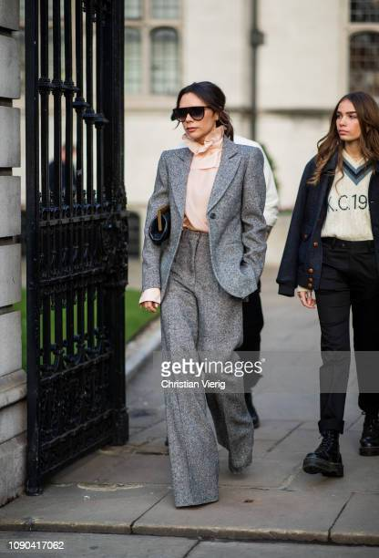 Victoria Beckham is seen outside Kent Curwen wearing grey suit with flared pants salmon colored ruffled blouse during London Fan Week Men's January...