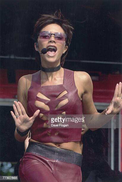 Victoria Beckham of British pop group the Spice Girls wears a revealing red catsuit during a live Radio 1 show in Middlesbrough's Stewart Park 6th...