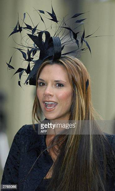 Victoria Beckham poses after her husband English Football captain David Beckham received an OBE 27 November from Britain's Queen Elizabeth II at...