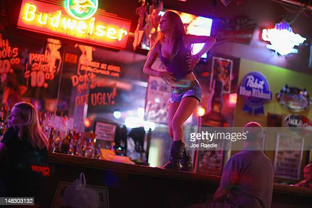 Victoria Brown dances on the bar at the Coyote Ugly saloon in the Ybor City neighborhood on July 12, 2012 in Tampa, Florida. The neighborhood was...