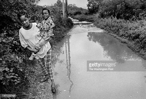 FILE Victoria Cummings carries her 5 yr old daughter Kadijah Cummings a half mile from the school bus stop to home via the unpaved flooded road in...