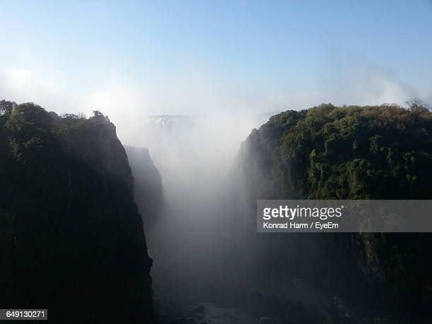 Victoria Falls Amidst Rock Formations Against Sky