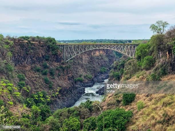 victoria falls bridge over the zambezi river - victoria falls stock pictures, royalty-free photos & images
