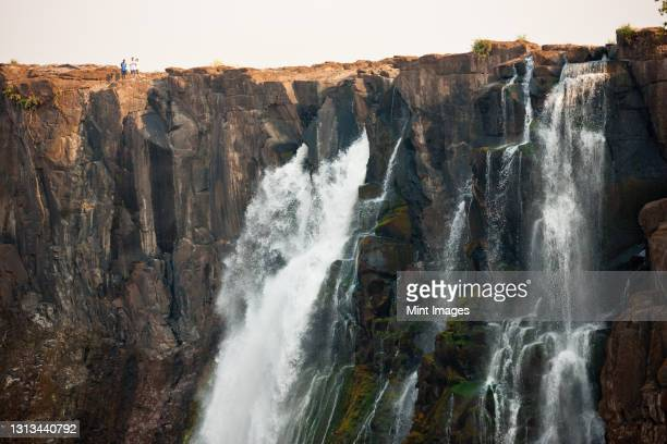victoria falls, huge waterfalls of the zambezi river flowing over sheer cliffs. - zambezi river stock pictures, royalty-free photos & images