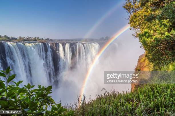 victoria falls with double rainbow - victoria falls stock pictures, royalty-free photos & images
