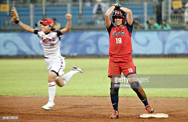 Victoria Galindo of the US right stands on base as Eri Yamada of Japan celebrates Japan's victory in the gold medal game of women's softball on day...