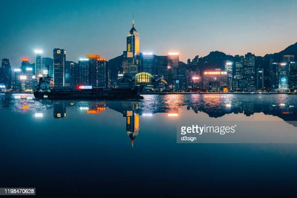 victoria harbour with panoramic view of illuminated hong kong city skyline at twilight - hong kong stock pictures, royalty-free photos & images