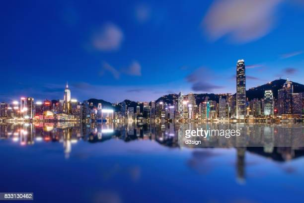 Victoria Harbour with panoramic view of illuminated Hong Kong city skyline at night