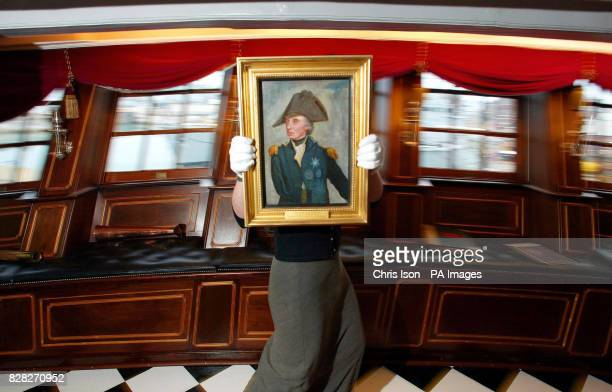Victoria Ingles Curatorial Project Officer of the Royal Navy Museum in Portsmouth carries a portrait of Admiral Lord Nelson in the Great Cabin aboard...