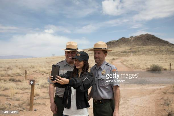 Victoria Justice poses with park rangers Dale Kissner and Dennis A Vasquez at Petroglyph National Monument on April 19 2018 in Albuquerque New Mexico