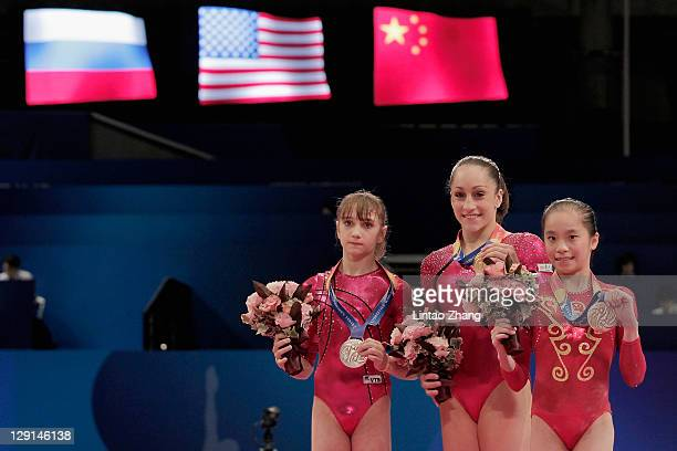 Victoria Komova of Russia,Jordyn Wieber of the United States and Yao Jinnan of China stand on the podium after the Women's All Around Final during...