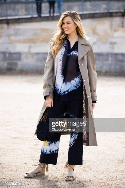Victoria Lee wearing a tie dye blue shirt with matching pants beige trench coat beige Dior sandals and Dior bag is seen outside Dior during Paris...