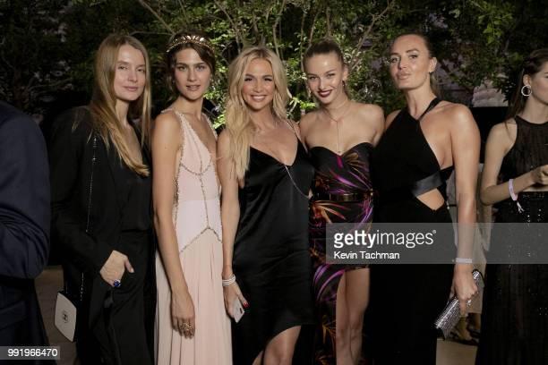 Victoria Lopyreva Kristina Romanova and Masha Hanson attend the amfAR Paris Dinner at The Peninsula Hotel on July 4 2018 in Paris France