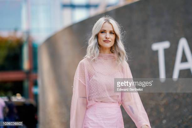 Victoria Magrath from In The Frow wears a Dior Saddle brown bag a pink lace mesh top a pink skirt black boots during London Fashion Week September...