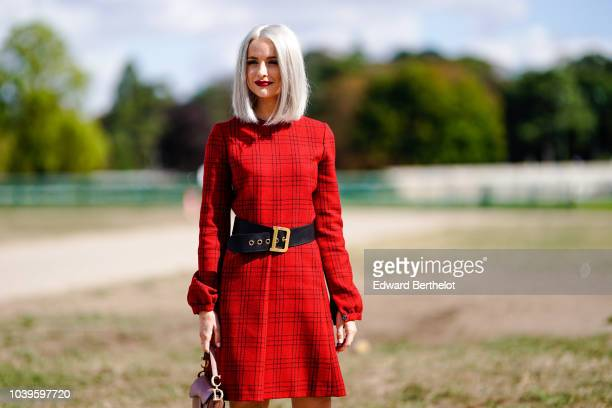Victoria Magrath wears a red dress and a black large leather belt outside Dior during Paris Fashion Week Womenswear Spring/Summer 2019 on September...