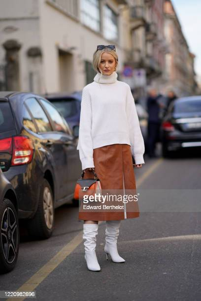 Victoria Magrath wears a white turtleneck wool pullover, a brown leather skirt, a Tod's orange leather bag, white pointy high heel boots, outside...