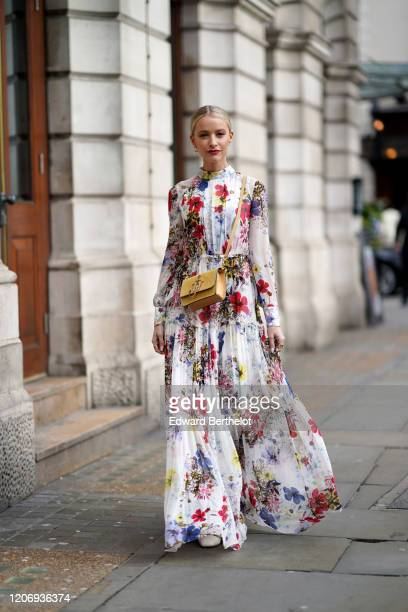 Victoria Magrath wears a yellow JW Anderson bag, a pleated and ruffled colored floral print dress, earrings, during London Fashion Week February 2020...