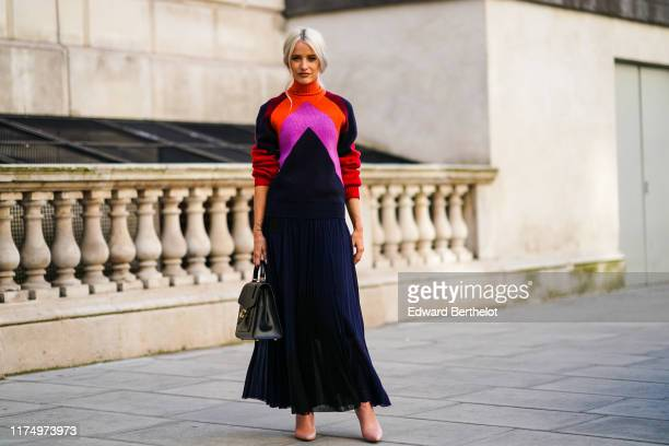 Victoria Magrath wears an orange red and pink wool pullover with a turtleneck a black lace pleated skirt a black leather bag during London Fashion...