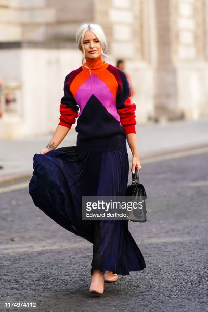 Victoria Magrath wears an orange red and pink wool pullover with a turtleneck, a black lace pleated skirt, a black leather bag, during London Fashion...