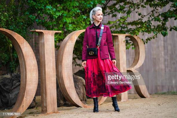 Victoria Magrath wears earrings, a red checked jacket, a Dior bag, a red skirt with printed patterns, black leather high heels shoes, outside Dior,...