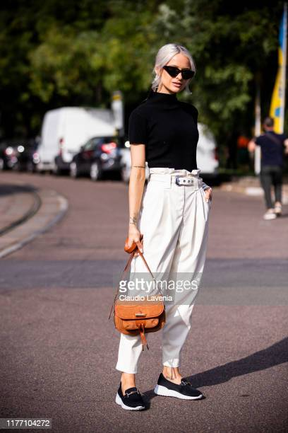 Victoria McGrath, wearing a black top, white pants, tan Tod's bag and black Tod's loafers, is seen outside the Tod's show during Milan Fashion Week...