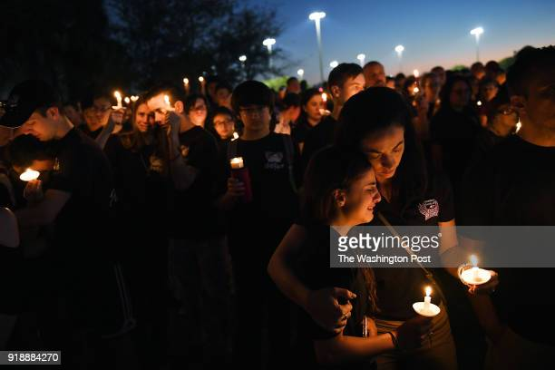Victoria Mondelli is embraced by her mother April Mondelli as people gather for a candlelight vigil in honor of the victims of the Marjory Stoneman...